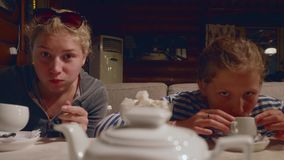 Two young caucasian girls drink tea and joke in cafe in evening after a hike. Two young girls drinks tea in cafe in evening after a hike stock video