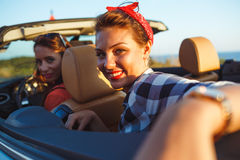 Two young girls driving a cabriolet. Two young happy girls driving a cabriolet Royalty Free Stock Photo