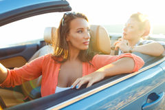 Two young girls driving a cabriolet. Two young happy girls driving a cabriolet Royalty Free Stock Images