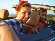 Two young girls driving a cabriolet. Two young happy girls driving a cabriolet Stock Photos