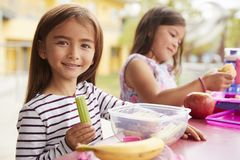 Two young girls eating packed lunches at school, close up royalty free stock photography