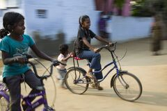 Two young girls enjoy riding bicycles