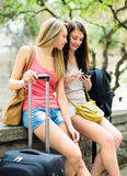 Two young girls finding path with smartphone Royalty Free Stock Images