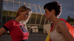 Two young girls, football fans, England against Spain, confrontation, wind, evening stadium in the background 50 fps stock footage
