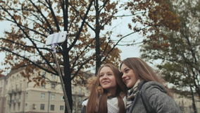 Two young girls friends do selfi autumn in one of the city streets. Two young girls friends do selfi autumn in one of the city streets stock video footage