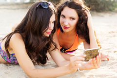 Two young girls friends together at the beach Stock Photo