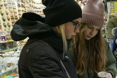 Two young girls in the gift shop choose souvenirs stock photos
