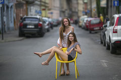 Two young girls girlfriend. Conceptual photo, a teen girl sits on a chair in the middle of the street Stock Photography