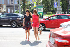Two young girls girlfriends cross the road Stock Photos