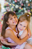Two young girls give each other gifts. In dresses on the bed hugs between Christmas gifts stock photography