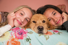 Two young girls with a golden retriever dog at home Royalty Free Stock Photo