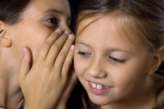 Two young girls in gossip. Two young beautiful girls talking on ear Royalty Free Stock Photo