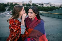 Two young girls gossip of somebody, close up. Spending good time together, modern urban life, communication and sale news, secrets and confidence concept Stock Photos