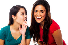 Two young girls gossiping Stock Image
