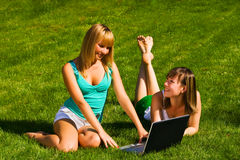 Two young girls on the grass with notebook. Two young girls on the green grass with notebook Royalty Free Stock Photos