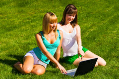 Two young girls on the grass with notebook. Two young girls on the green grass with notebook Royalty Free Stock Image
