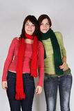 Two young girls in green and red scarfs Royalty Free Stock Photography