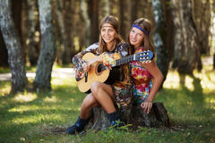 Two young fashion girls with guitar in a summer forest Stock Photo