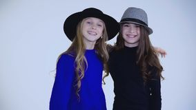 Two young girls in hat dancing and posing at camera on background. Full HD stock video