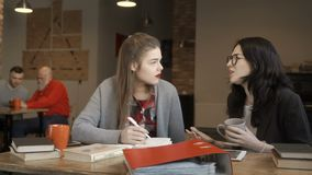 Two young girls have a break during preparation to university exams and talking. Two students are talking sitting at the table. Pretty girls have a break during stock footage
