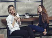 Two young girls have a coffee time at the counter in a cafe Royalty Free Stock Photography
