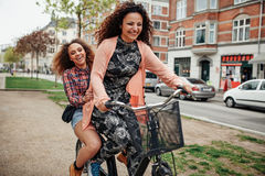 Two young girls having fun on bicycle Royalty Free Stock Photo