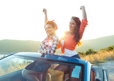 Two young girls having fun in the cabriolet outdoors. Two young happy girls having fun in the cabriolet outdoors Stock Photography