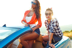 Two young girls having fun in the cabriolet outdoors. Two young happy girls having fun in the cabriolet outdoors Stock Photos