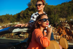 Two young girls having fun in the cabriolet outdoors. Two young happy girls having fun in the cabriolet outdoors Royalty Free Stock Photos