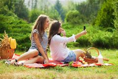 Two young girls having fun on the picnic, making selfie on a smartphone Royalty Free Stock Images