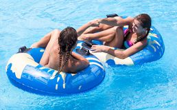Two women in the swimming pool. Two young girls having fun in the swimming pool Royalty Free Stock Photo
