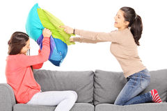 Two young girls having a pillow fight seated on couch Royalty Free Stock Photos