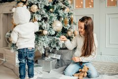 Two girls with santa hat laying in front of the christmas tree. Two Young Girls havung fun In Front Of Christmas Tree Royalty Free Stock Photography