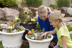 Two young girls helping to make fairy garden in a flower pot. Outdoors Royalty Free Stock Photo