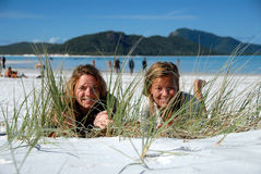 Two young girls hiding behind grass on beach. Two beautiful young women hiding behind grass on the beach in the sand at beach Stock Photo