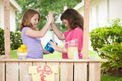 Two young girls high fiving. Two young girls give each other a high five as they look into their money bucket, indicating the success of their lemonade stand Royalty Free Stock Photography