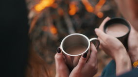 The two young girls hold cups with cacao and rest by bonfire. stock footage