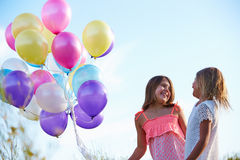 Two Young Girls Holding Bunch Of Colorful Balloons Outdoors Royalty Free Stock Photos