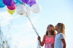 Two Young Girls Holding Bunch Of Colorful Balloons Outdoors Stock Photo
