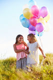 Two Young Girls Holding Bunch Of Colorful Balloons Outdoors Stock Image
