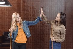 Two young girls holding cues and giving high five to each other. At bar stock photography