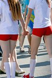 Two young girls holding hands and standing with their backs. Two young girls in shorts and golfs holding hands and standing with their backs royalty free stock photos