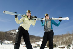 Two young girls holding there skis in the air Royalty Free Stock Photography