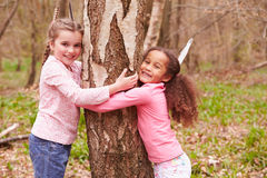 Two Young Girls Hugging Tree In Forest Stock Image