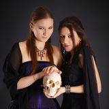 Two young girls with a human skull Royalty Free Stock Photos