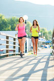 Two young girls jogging outdoors Stock Image
