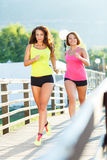 Two young girls jogging outdoors Stock Photography