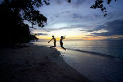Two young girls jumping by the ocean at sunset royalty free stock photos