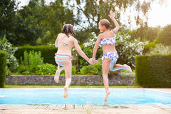 Two Young Girls Jumping Into Swimming Pool Together Royalty Free Stock Images