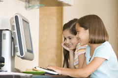 Two young girls in kitchen with computer smiling Royalty Free Stock Photo